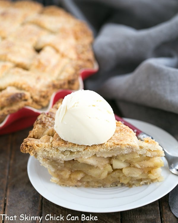 A slice of Deep Dish Apple Pie on a white dessert plate with a scoop of ice cream on top