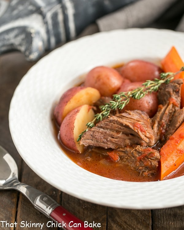 Easy Pot Roast in a shallow white bowl with a sprig of thyme