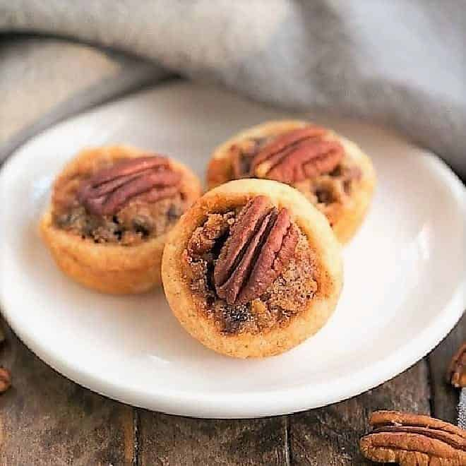 Pecan Tassies on a small white oval plate