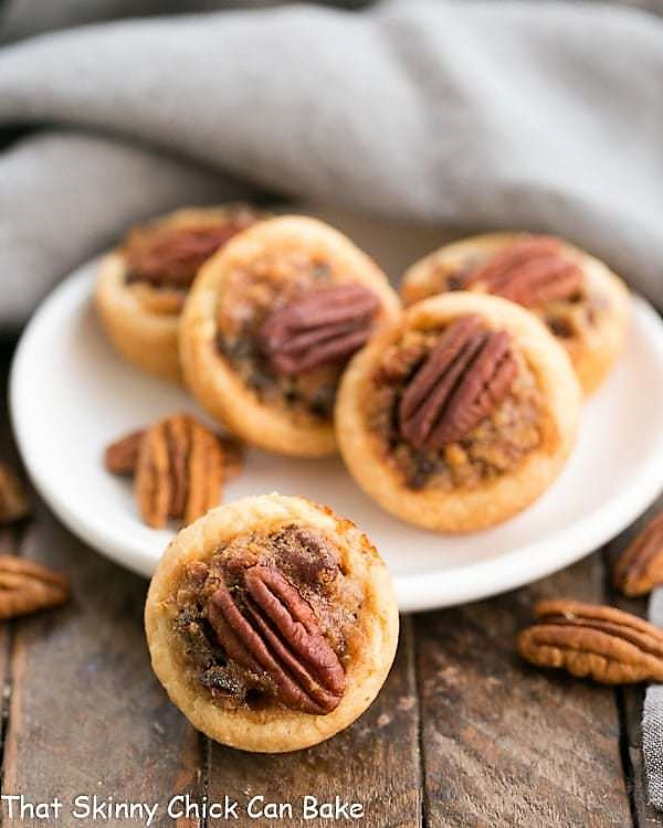 Pecan Tassies on a white plate with pecan halves