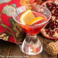 Pomegranate Champagne Cocktail garnished with orange slices in a small cocktail glass