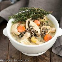 A bowl chicken and wild rice soup garnished with thyme