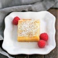 Gooey Butter Bars dessert on a plate with fresh raspberries