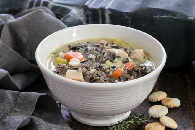 Wild Rice Soup in a white bowl with a spirg of thyme and oyster crackers