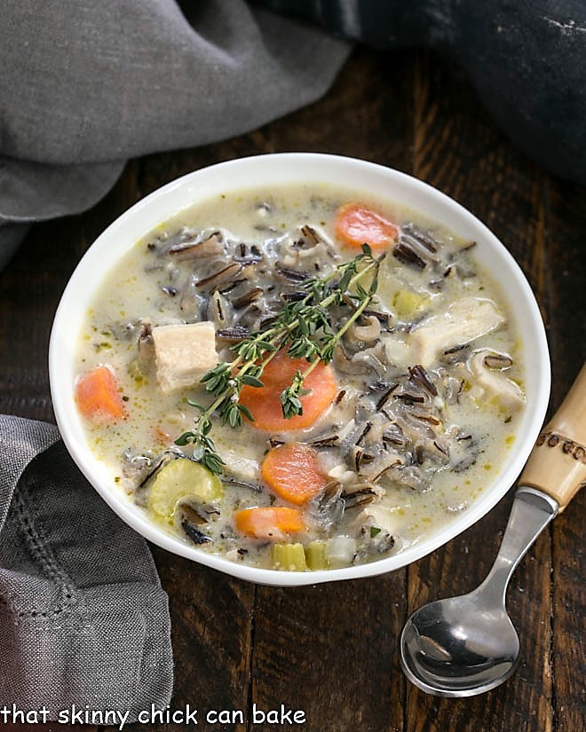 Overhead view of a bowl of wild rice soup with a bamboo handle spoon