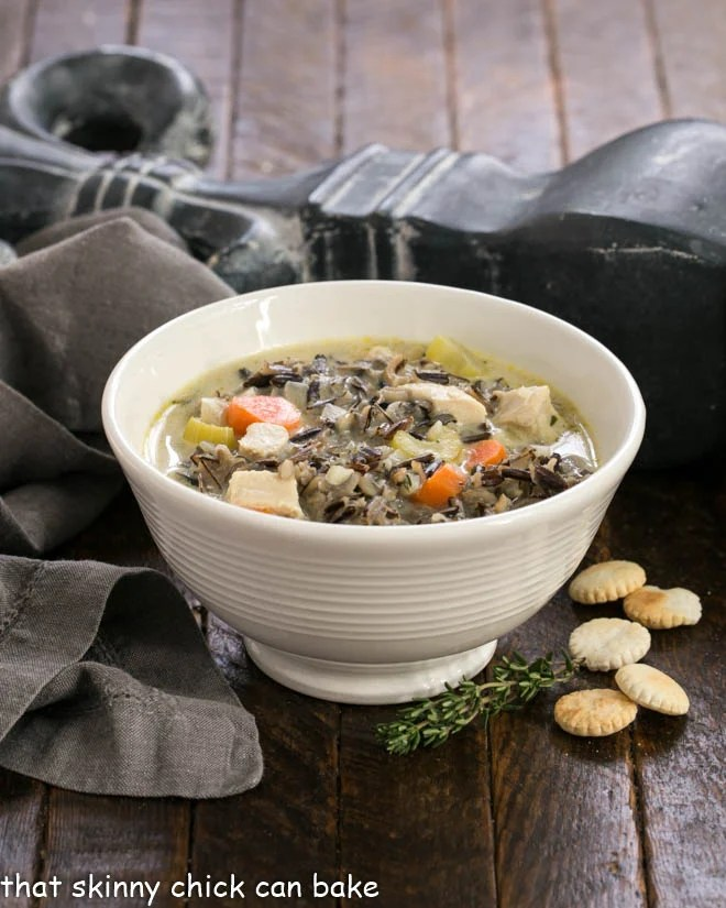 Wild Rice Soup in a white bowl with oyster crackers and a sprig of thyme