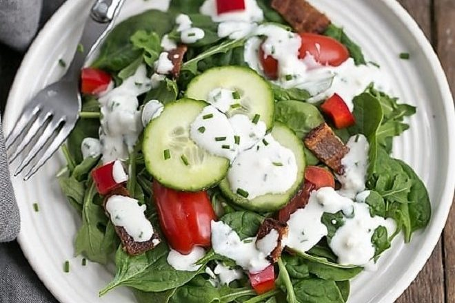 Overhead view of a green salad with blue cheese salad dressing on a round white plate
