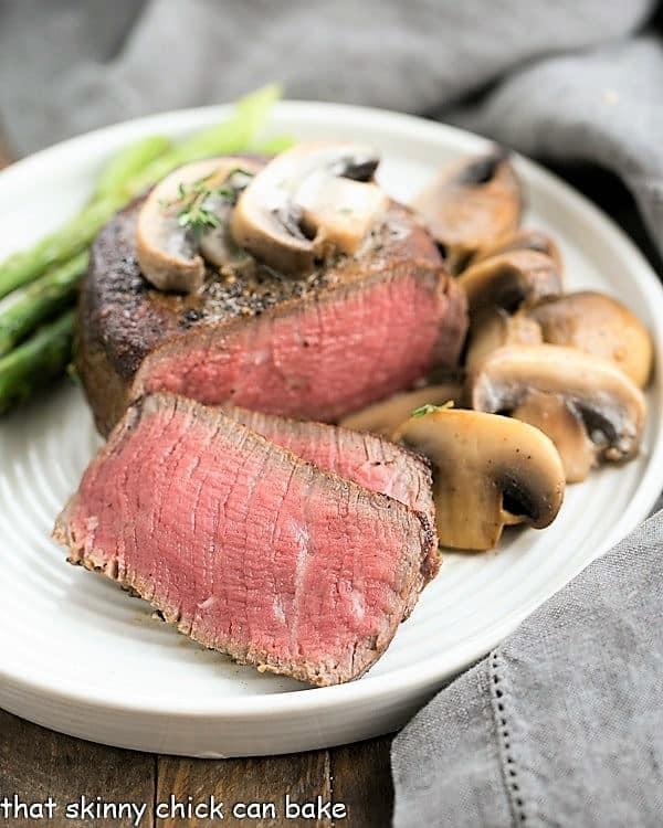 Mushroom Topped Pepper Steak sliced on a white dinner plate