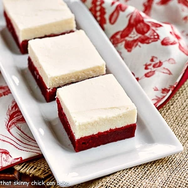 Red Velvet Brownies with White Chocolate Icing on a white rectangular serving tray