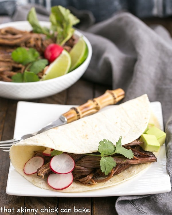 Slow Cooker Carne Asada in a tortilla on a square white plate