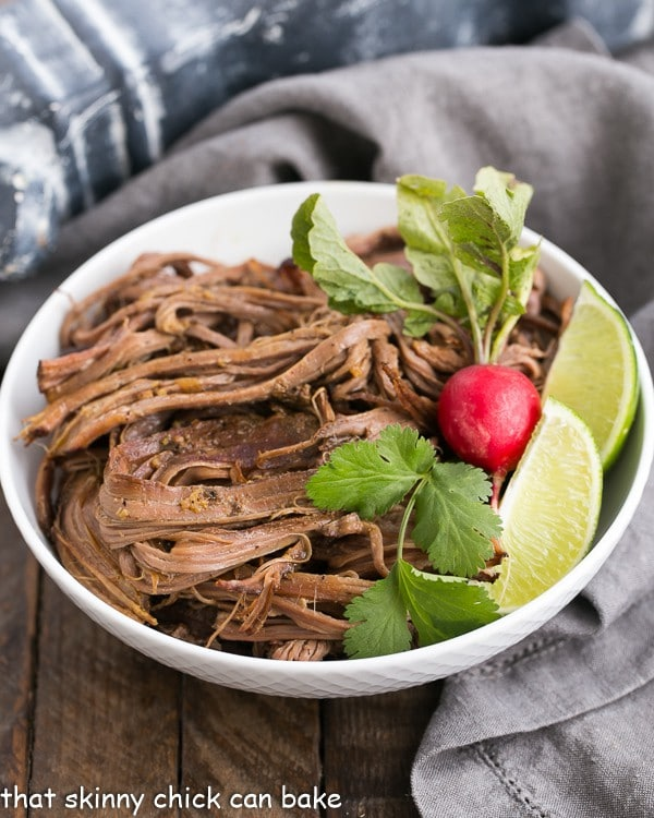 Slow Cooker Carne Asada in a white bowl with a radish and lime wedges