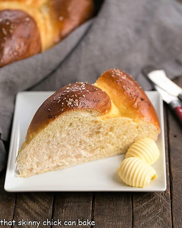slice of Braided Easter Bread on a square white plate with 2 pats of butter