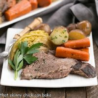 Square white plate with braised corn beef, cabbage, potatoes and carrots