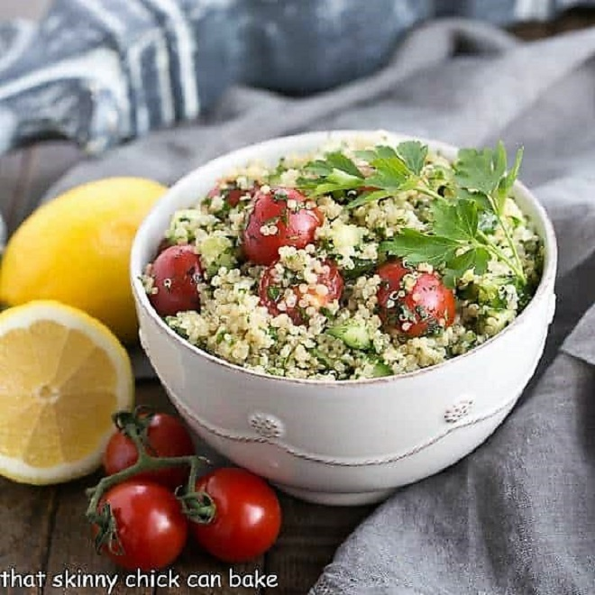 Bowl of quinoa tabbouleh in a white bowl with a lemon and cherry tomatoes