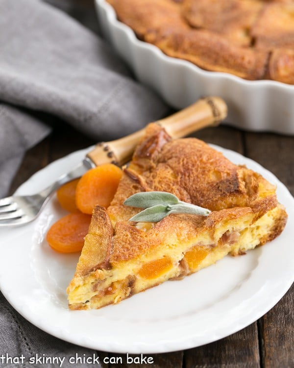 A slice of Apricot Prosciutto Strata topped with sage leaves in front of a casserole dish