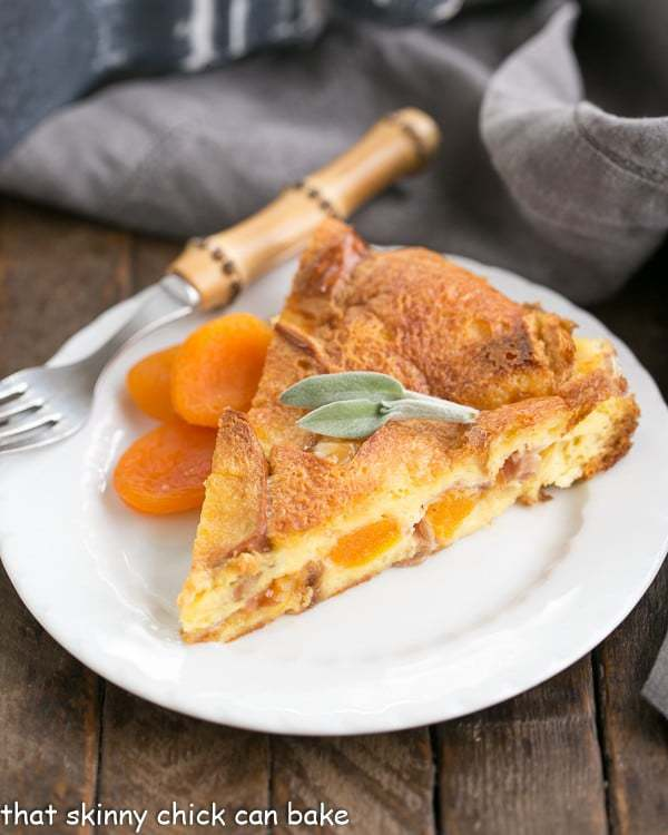 Slice of Apricot Prosciutto Strata on a white plate with dried apricots and bamboo handle fork