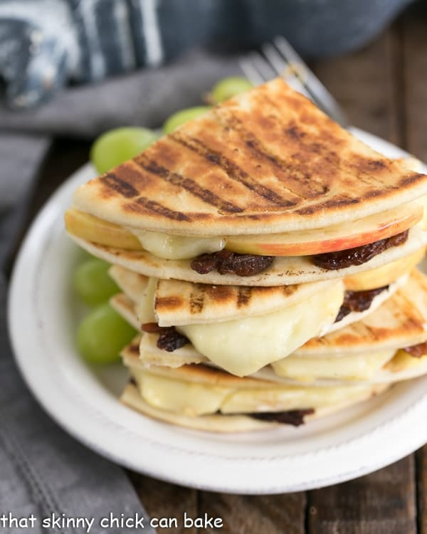 Bacon Apple & Brie Panini quarters stacked on a white plate with grapes