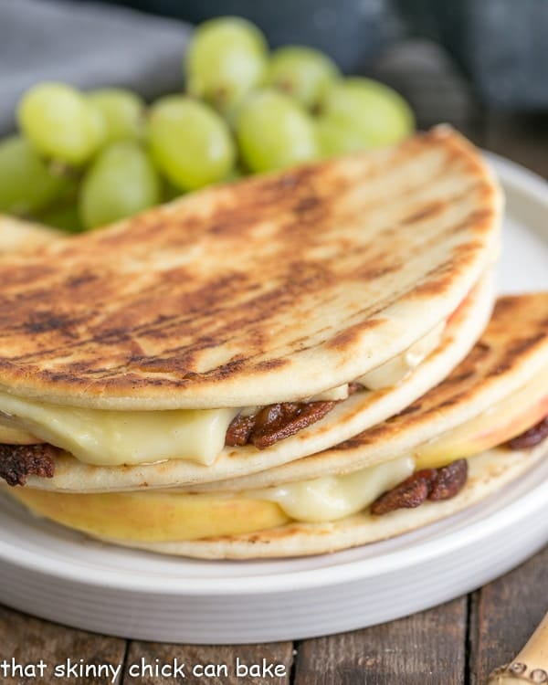 Bacon Apple & Brie Panini halves on a white plate with grapes