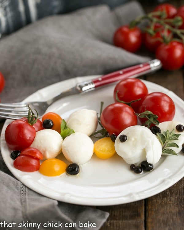 Side view of a Burrata Caprese Salad on a white plate with a fork