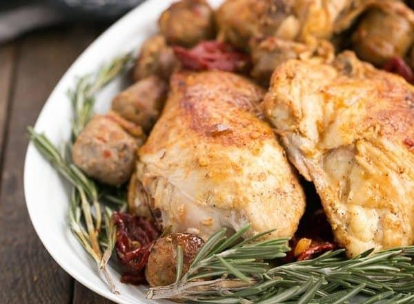 Chicken Scarpariello on a serving platter with rosemary garnish