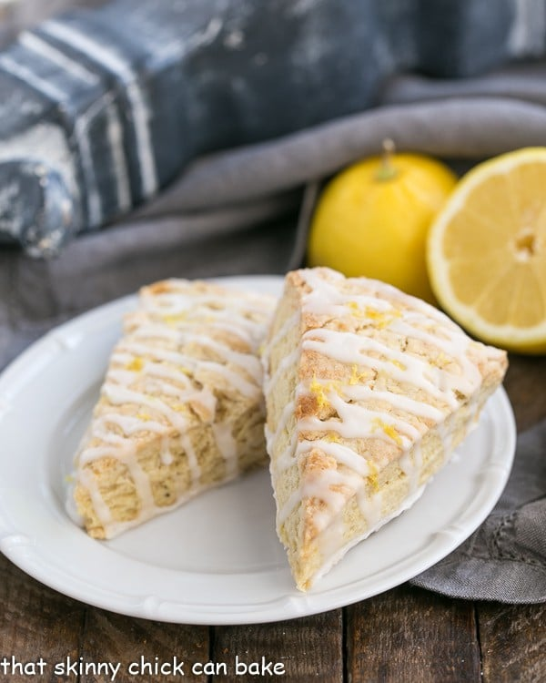 Two Glazed Lemon Tea Scones on a white plate with lemons in the background