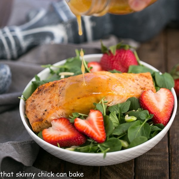 Dressing pouring over a Salmon Watercress Salad in a white salad bowl