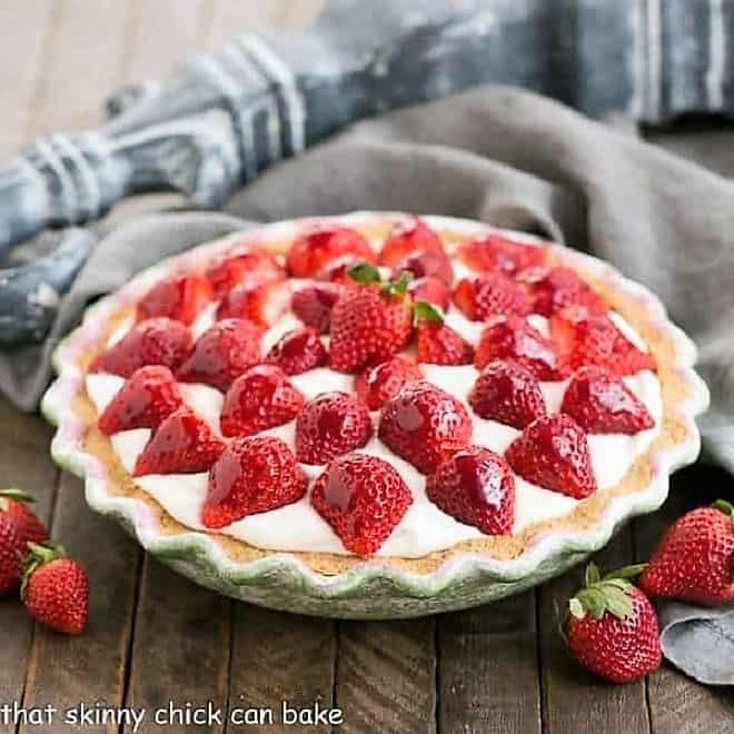 Strawberry Cream Pie  in a cerami pie plate surrounded by fresh strawberries