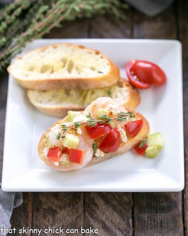 One Greek Shrimp Crostini next to two garlic toasts on a white plate