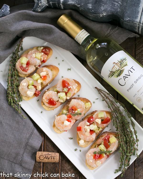 Greek Shrimp Crostini lined up on a white ceramic platter next to a bottle of white wine