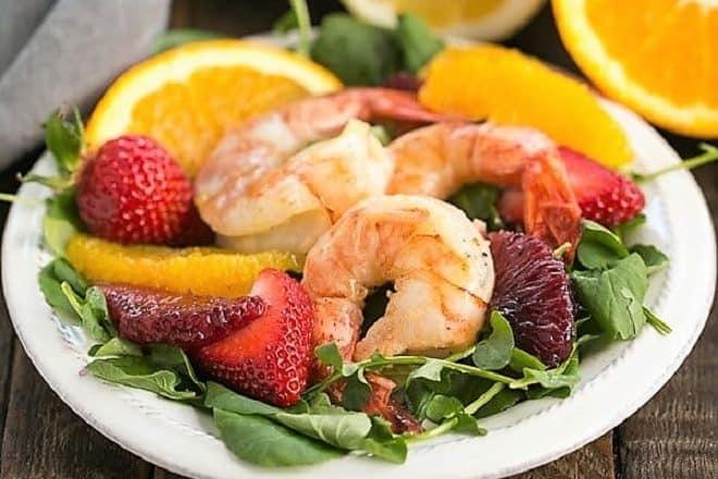 Shrimp salad on a white plate with citrus halves