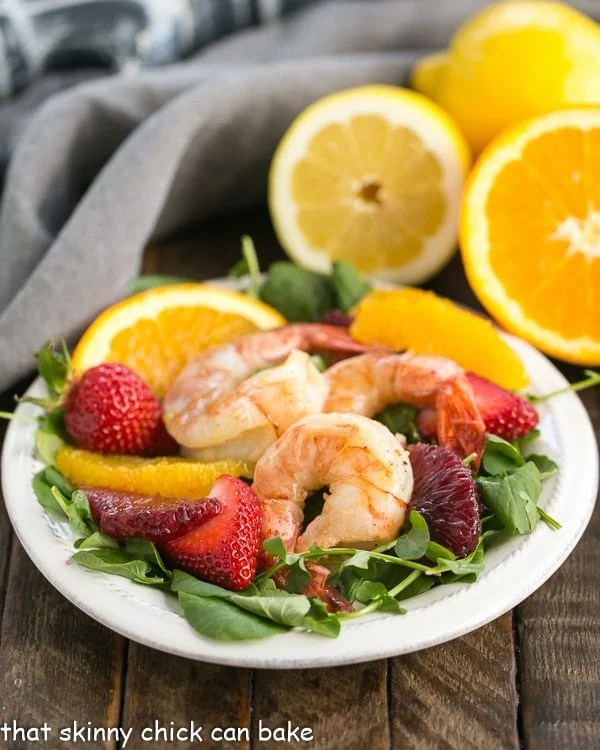 Shrimp, Orange, & Watercress Salad with Citrus Vinaigrette on a white plate with cut citrus in the background