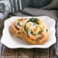 Two Feta and Spinach pinwheets on a square white plate