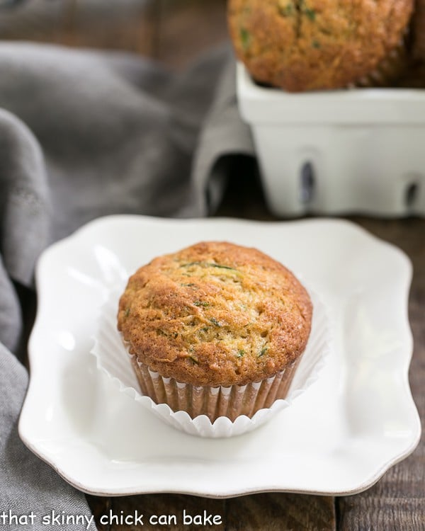 Cinnamon Zucchini Muffins on a white plate with a square basket of muffins in the background