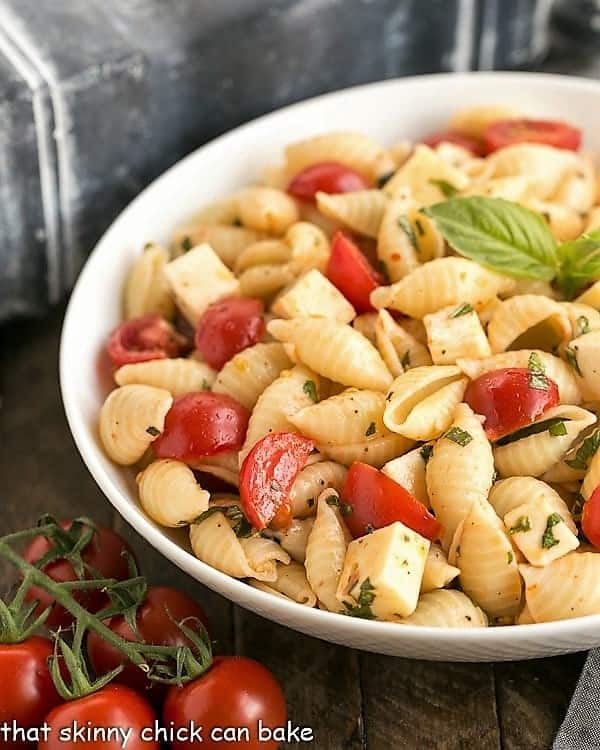 Tomato Basil Pasta Salad with Mozzarella & Fontina in a white ceramic serving bowl