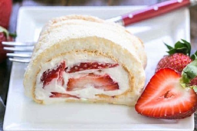 Slice of strawberry filled meringue roulade on a square white plate with a fork and berry garnish