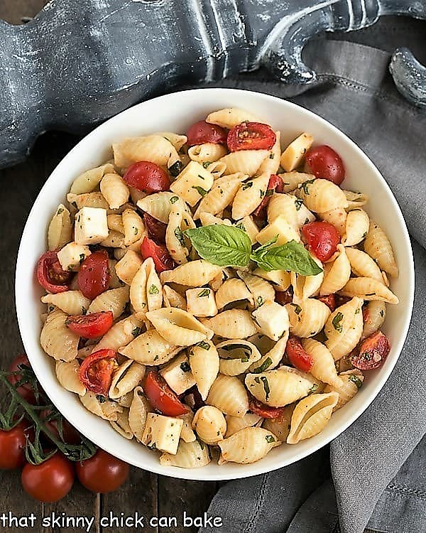 Overhead view of Tomato Basil Pasta Salad with Mozzarella & Fontina in a white serving bowl