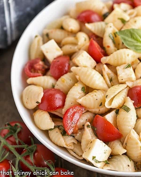 Tomato Basil Pasta Salad with Mozzarella & Fontina close view in a white serving bowl
