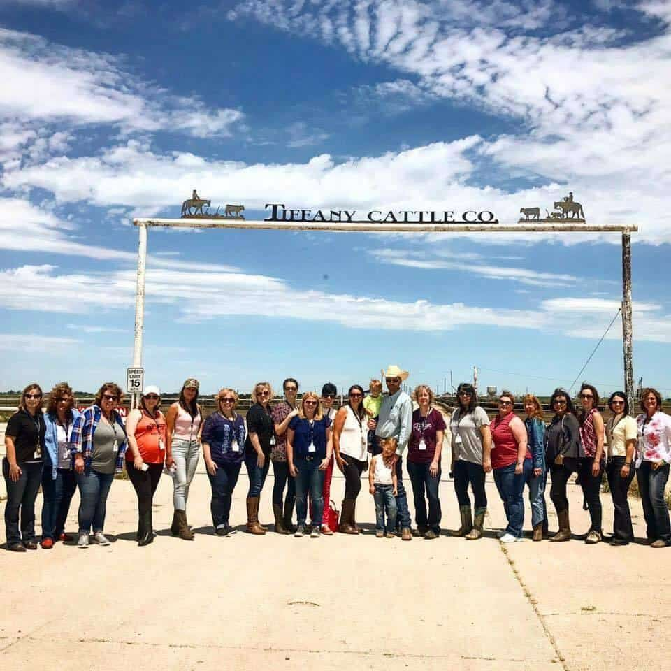 A group of people standing in front of the sign to a cattle ranch