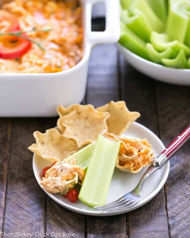 Buffalo Chicken Dip Recipe on a small white plate with tortilla chips and celery sticks