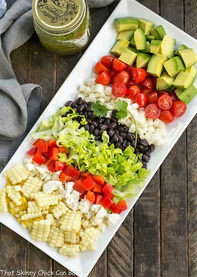 Overhead view of Mexican Chopped Salad on a rectangular white tray plus dressing in a canning jar