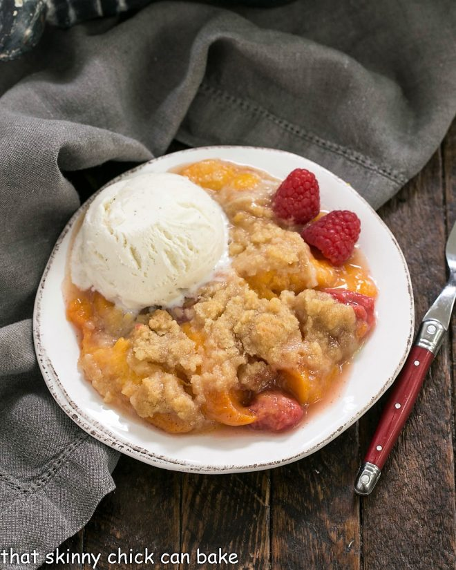 Overhead view of peach raspberry crisp topped with a scoop of ice cream