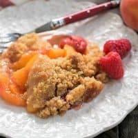 Peach raspberry crisp on a decorative white plate garnished with fresh raspberries
