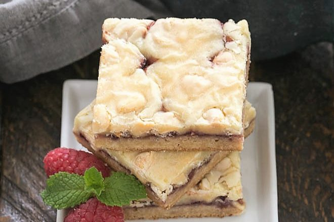 A stack of 3 white chocolate raspberry bars on a square white plate with raspberries and mint to garnish