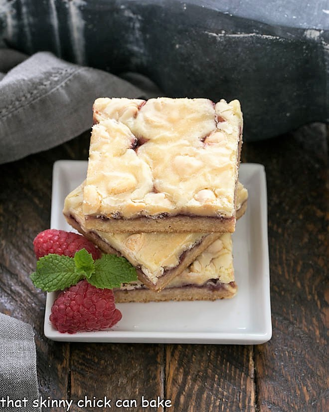 A stack of 3 White Chocolate Raspberry Bars on a small white ceramic plate