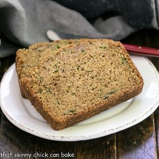 Two slices of zucchini bread on a round white plate with a red handle knife