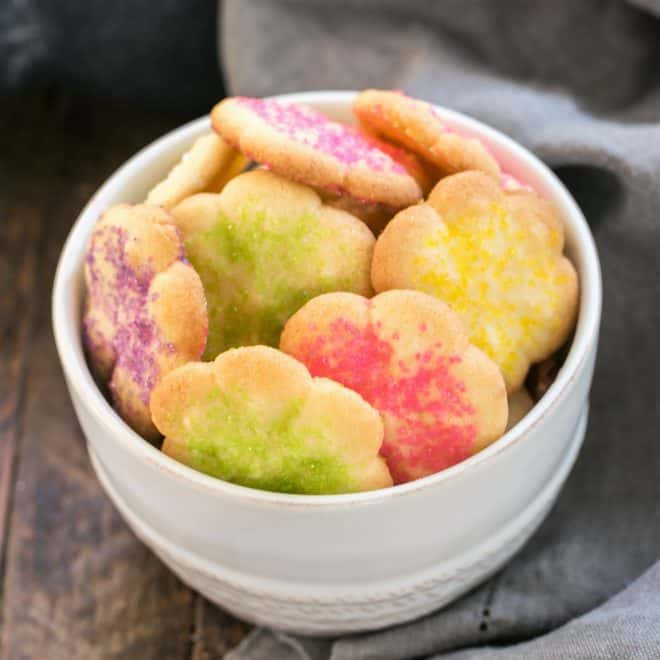 Classic Vanilla Spritz Cookies coated in spinkles in a white bowl