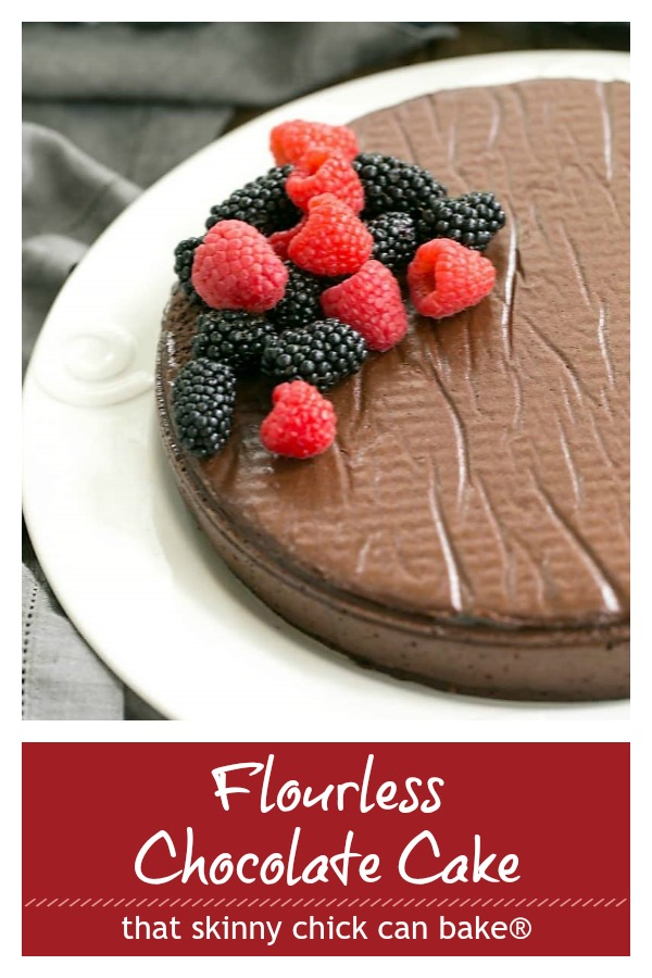 Flourless Chocolate Cake on a white serving plate with a berry garnish
