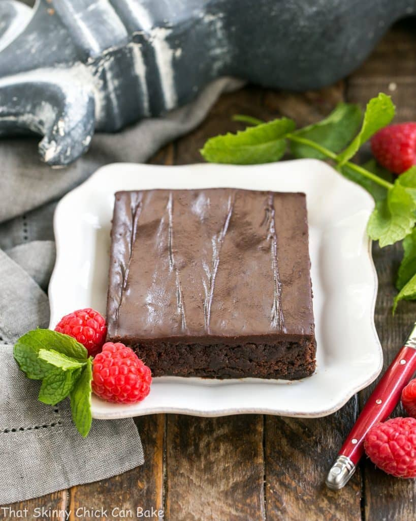 Slice of Fudgy Chocolate Sheet Cake with Cocoa Icing on a square white plate with raspberries and mint