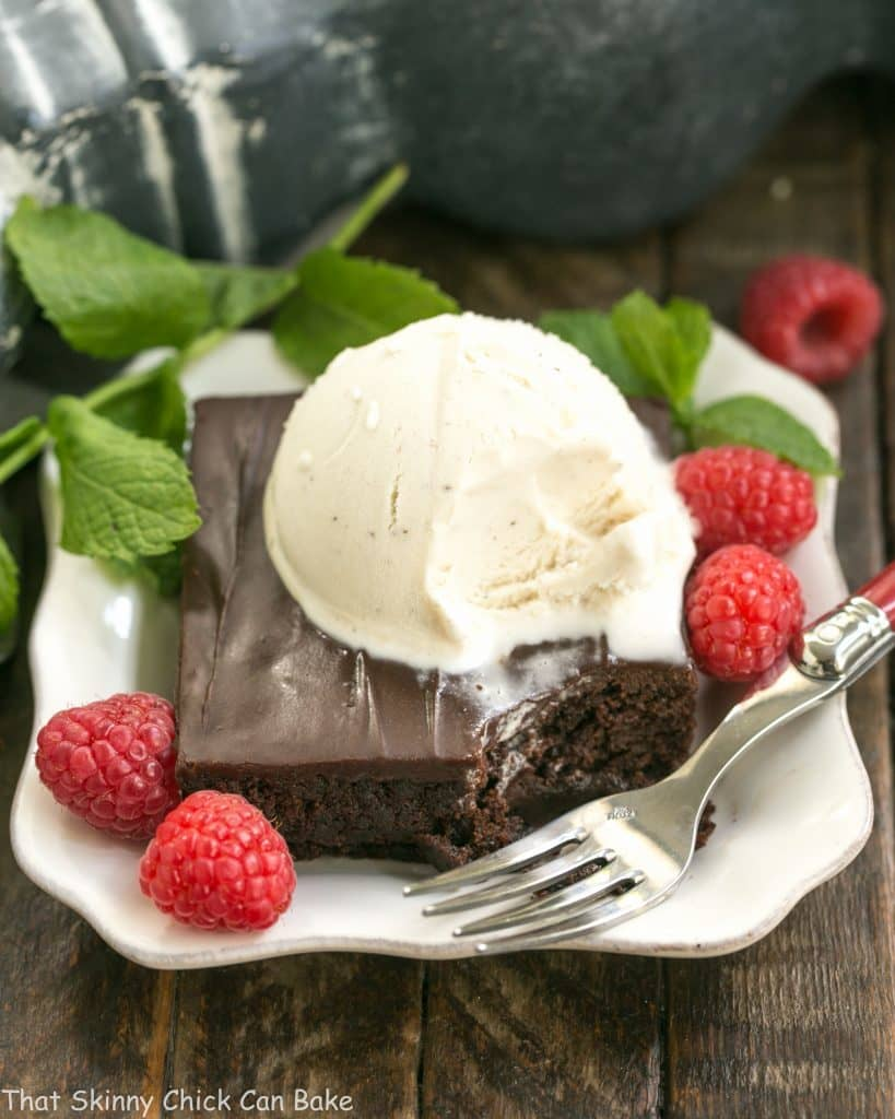 Fudgy Chocolate Sheet Cake with Cocoa Icing on a white dessert plate with ice cream, mint and raspberries
