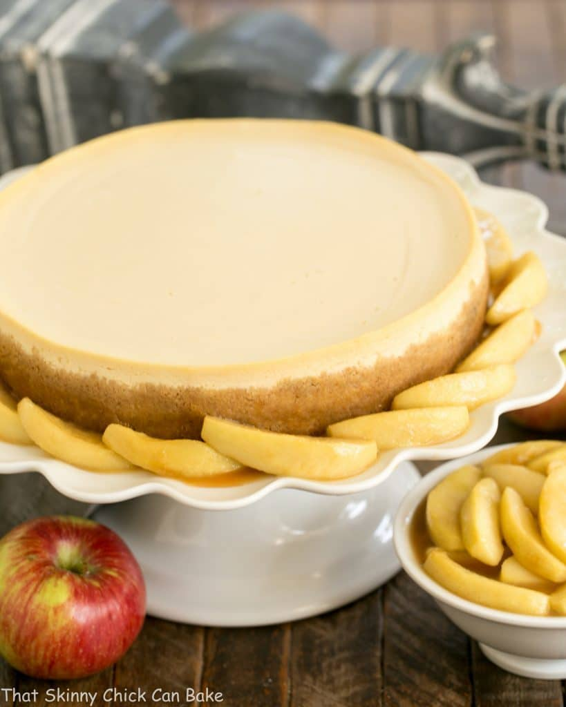 Easy Sour Cream Cheesecake with Caramel Apples on a white ceramic cake stand